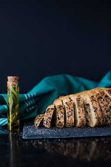 Rosemary in test tube and slices of whole grain baked bread slices on black background
