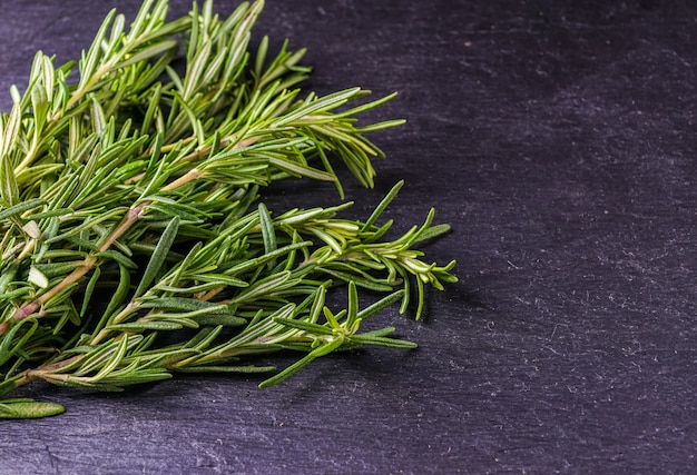 Rosemary and thyme on the black background, top view.