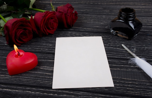 Розы, свеча, открытка, перо и чернильница