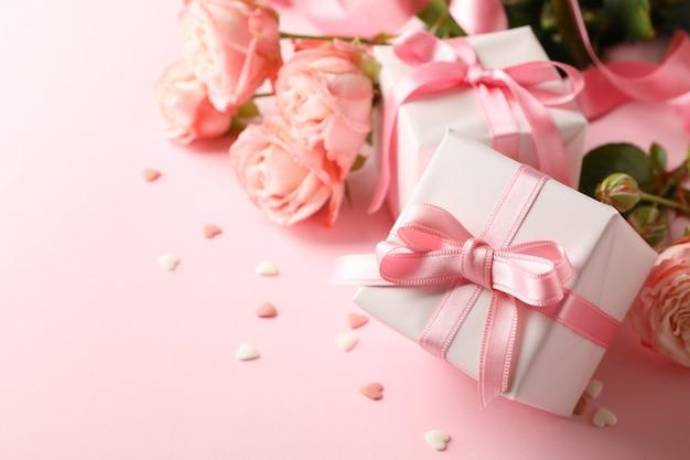 ピンクの背景にバラとギフトボックス、テキスト用のスペース
