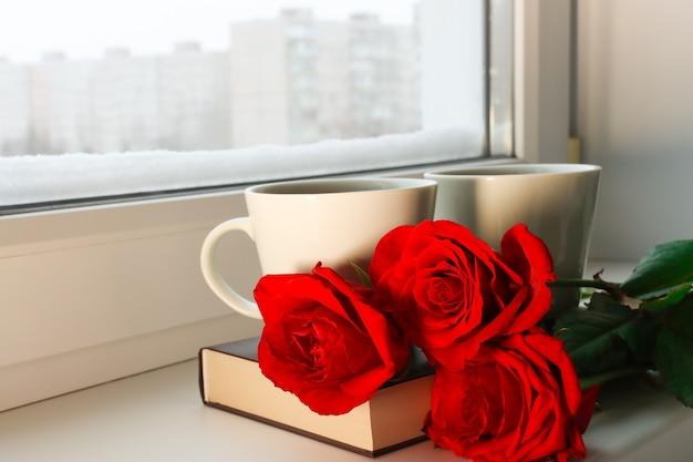 Розы и горячий чай на подоконнике со снегом - концепция романтического времени вместе дома