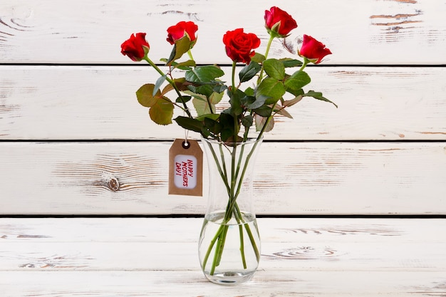 バラと母の日のタグラベルと花瓶の花は、ママへのママの花のギフトのプレゼントを作り続けています
