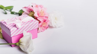 Roses and pink lily flowers with gift box on white background