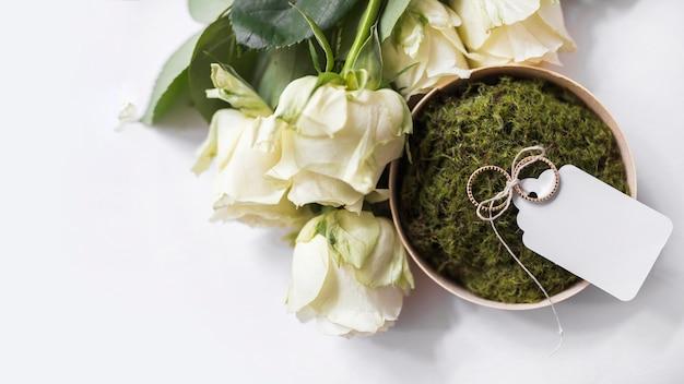 Розы и обручальные кольца с белой биркой на мхе в миске