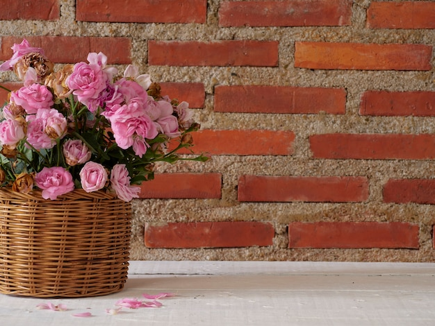 Roses in basket on wooden table against brick wall