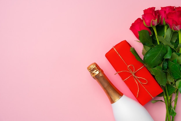 Roses bouquet, bottle of champagne and gift box flat lay top view