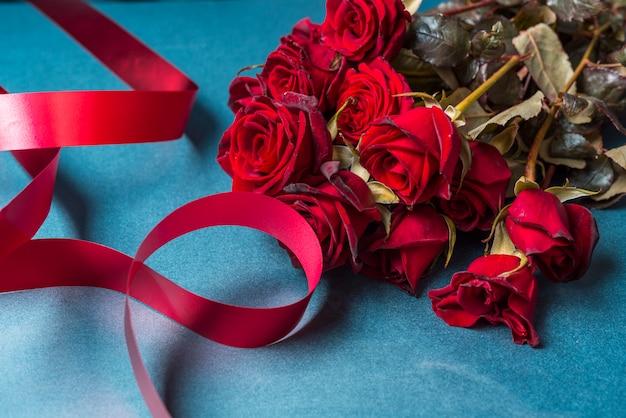 テーブルに赤いリボンとバラの花束