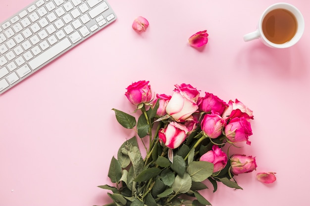Roses bouquet with tea cup and keyboard