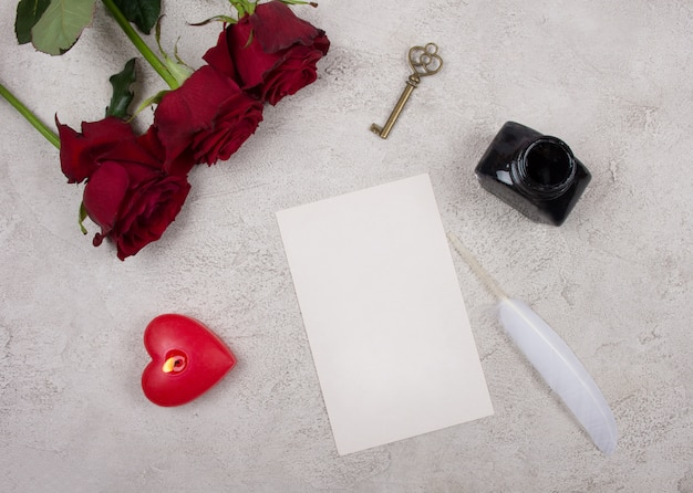 Roses, a candle, a key, a card, a feather and an inkpot