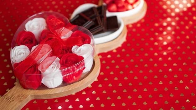 Розы, шоколадные конфеты и сладости на тарелках в форме сердца. сервировка праздничного стола для свидания влюбленных. красный фон