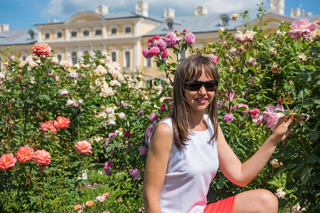 Roses garden and smiling happy woman on sunny summer day.
