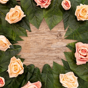 Roses and green leaves on old wood background