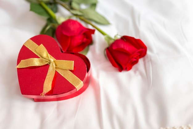 Roses and heart shaped box of candies in bed