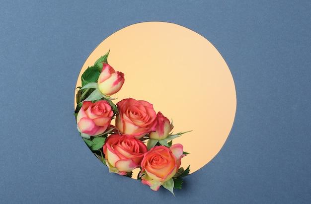 Розы в круглой рамке из серой бумаги на желтой поверхности