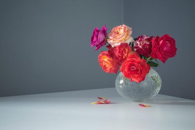 회색 배경에 유리 꽃병에 장미