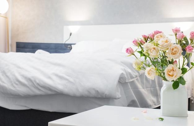 현대 침실에서 배경 침대에 꽃병에 장미