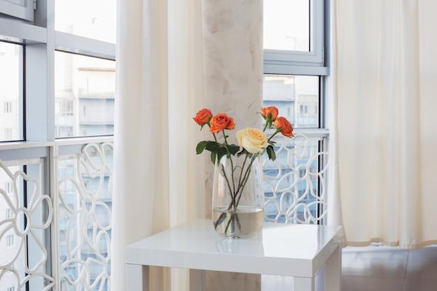 Розы в вазе на белом столе