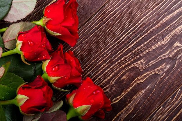 Розы в каплях воды. мокрые цветы на дереве. свежесть праздничного утра. удовольствие от подарка.