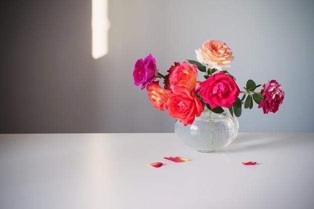 회색 배경에 흰색 꽃병에 장미