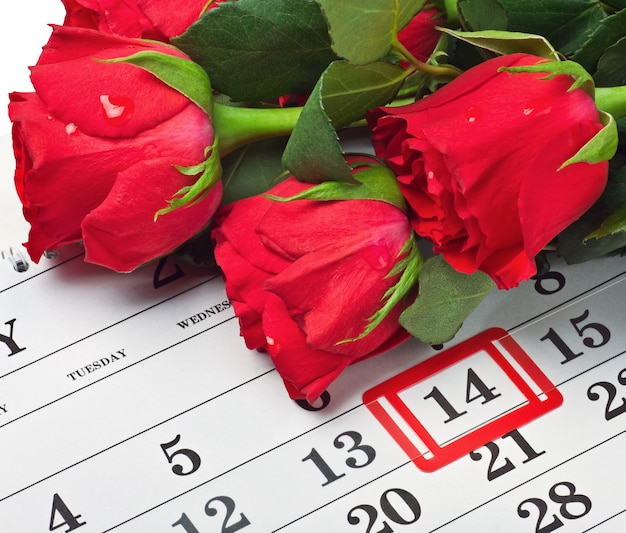 Roses lay on a calendar with the date of february 14 valentine's day
