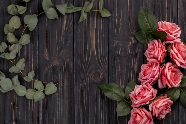 Roses and leaves on wooden tabletop