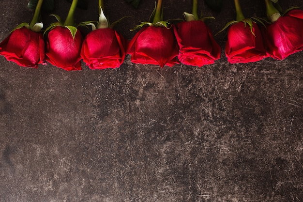 Roses lie on a dark marble table. big beautiful bouquet of red roses. texture colors. a gift for a wedding, birthday, valentine's day. space for text and design. flat lay, copyspace.