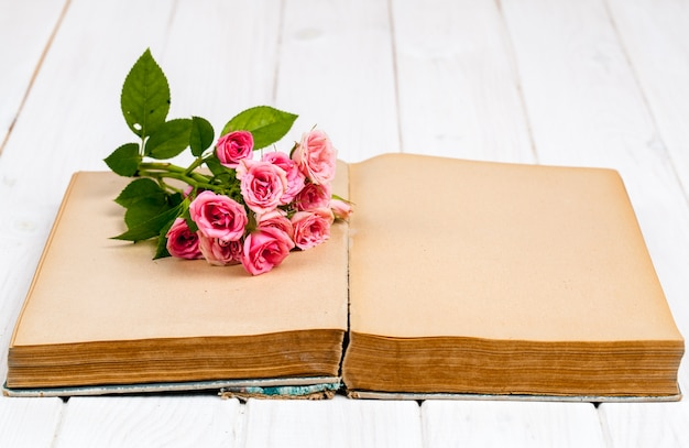 白い木製の背景上の古い本のバラ。フラワーズ