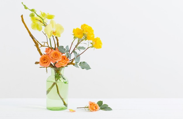 Roses and orchids in green glass vase on white background