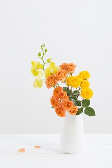 Roses and orchids in vase on white background