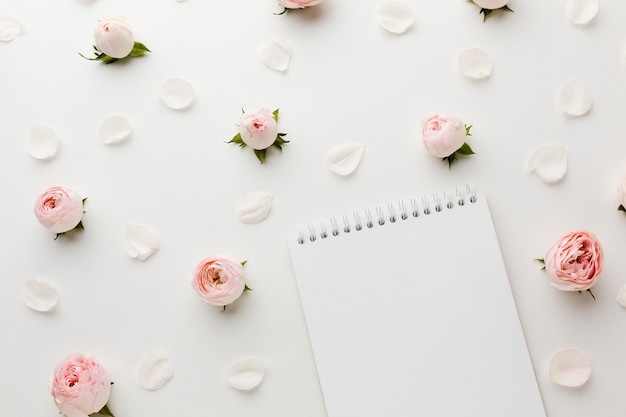 Roses and petals with notepad top view