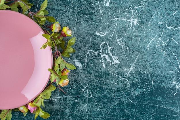 Rose sotto il piatto, su sfondo blu. h