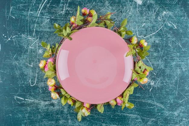 Rose sotto il piatto, su sfondo blu. foto di alta qualità