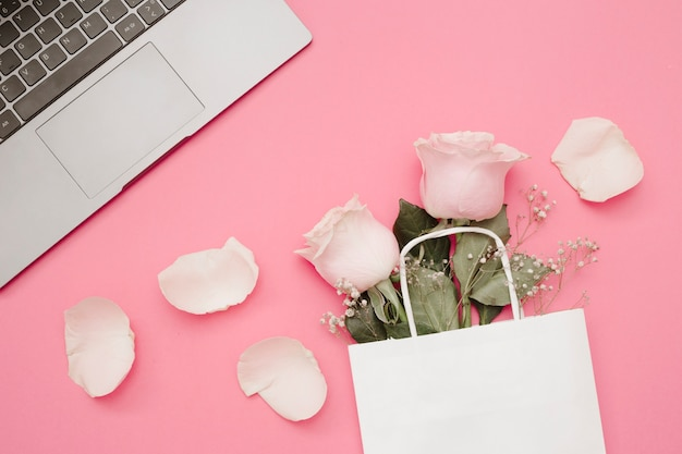 Roses in the shopping bag and laptop on pink background