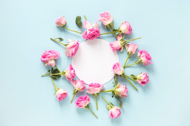 Roses surrounding blank circular frame on blue backdrop