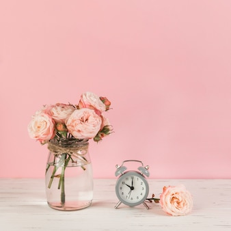 Roses vase near the alarm clock on wooden desk against pink background
