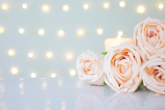 Roses on white against glow bokeh lights background with copyspace clean valentine day