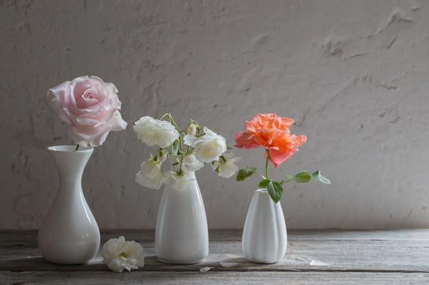 Roses in white vases on old background