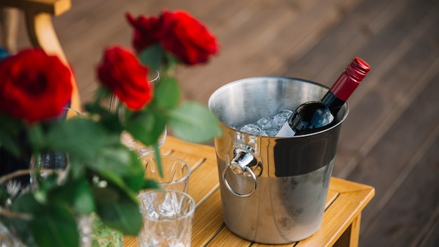 Roses and wine bottle in ice bucket on table