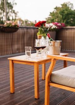 장미; 레스토랑에서 나무 테이블에 와인 글라스와 얼음 양동이