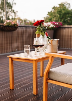 Roses; wine glass and ice bucket on wooden table in restaurant