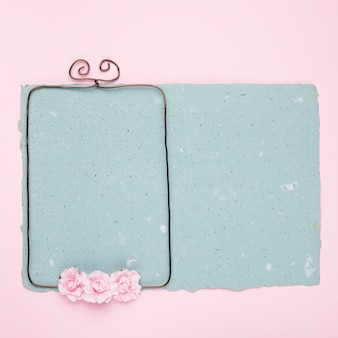 Roses on wired frame over the blue paper on pink backdrop