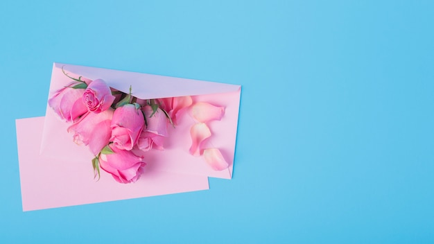 Roses with envelope on blue table
