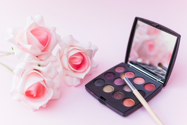 Roses with makeup brush and eyeshadow palette on pink backdrop