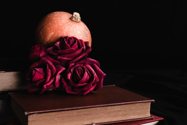 Roses with pumpkin on books