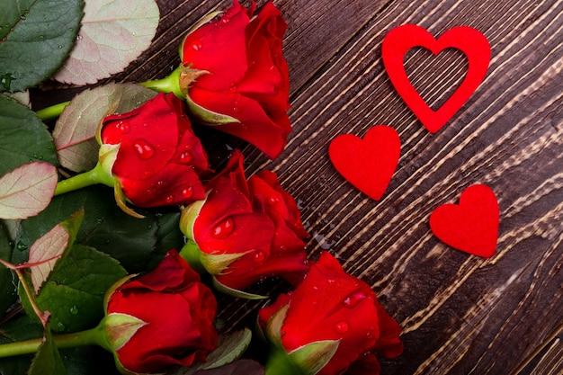 Розы с каплями воды. живые цветы возле сердечек. создайте праздничное настроение. шаблон романтического подарка.