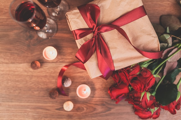 Roses on a wooden table with a gift with a red bow