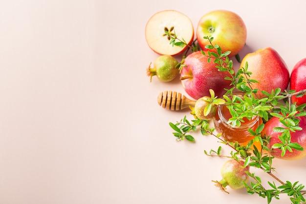 Рош ха-шана, концепция праздника еврейского нового года с традиционными символами, яблоками, медом, гранатом на пастельно-розовом абрикосовом столе. скопируйте космический фон