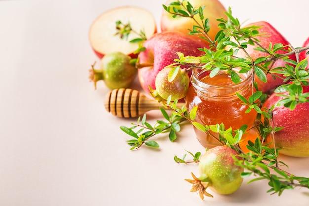Rosh hashana、パステルピンクのアプリコットテーブルに伝統的なシンボル、リンゴ、蜂蜜、ザクロを使ったユダヤ人の新年の休日のコンセプト。スペースの背景をコピーする