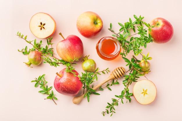 Rosh hashana、パステルピンクのアプリコットテーブルに伝統的なシンボル、リンゴ、蜂蜜、ザクロを使ったユダヤ人の新年の休日のコンセプト。フラットレイの背景