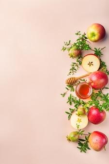 Рош ха-шана, концепция праздника еврейского нового года с традиционными символами, яблоками, медом, гранатом на пастельно-розовом абрикосовом столе. плоская планировка, копия космического фона